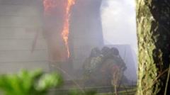 Firemen hose down huge flames - stock footage