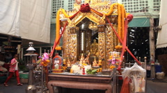 A porter walks past a Buddhist shrine at Yodpiman market Stock Footage