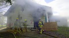 Firefighters walk around smoking house - stock footage