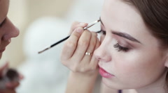 Makeup artist corrects the eyebrow line of model with the brush - stock footage
