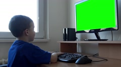 Young child boy works on computer on the table in room - green screen monitor Stock Footage