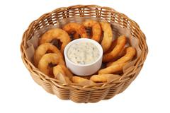 Onion rings in deep wicker cookware isolated on white background. Stock Photos