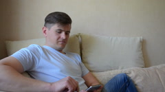 Handsome man using smart phone at home sitting in the couch - stock footage
