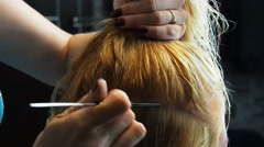 Hair stylist parting blonde hair with comb - stock footage