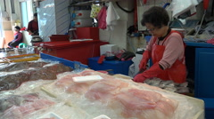 A senior lady cuts fish at South Korea's largest fish market in Busan Stock Footage