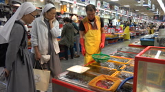 Christian nuns buy fresh seafood at a fish market in South Korea Stock Footage