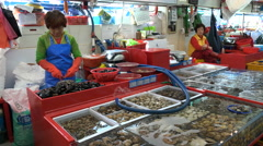 Woman removes mussels from their shells at a fish market in South Korea - stock footage