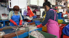 Female workers cutting cleaning fish, seafood market, manual labor, South Korea Stock Footage