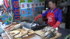Grilling fresh fish on the barbecue, street food market in South Korea, Asia Arkistovideo