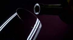 The bottle of wine, the wine is poured into a glass, black, closeup, slowmotion Stock Footage