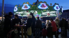 Walking and relaxing next to a carousel at the Children's Advent fair in Graz - stock footage