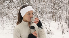 Beautiful brunette pours coffee from a thermos for a walk in winter Stock Footage