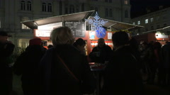 Tourists gathered in front of a drinks stall at the Christmas market in Graz Stock Footage