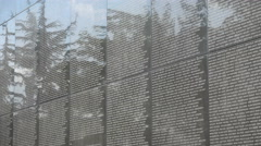 Trees reflect on wall of remembrance at United Nations cemetery in South Korea - stock footage