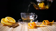 Pouring Blooming Tea with Cinnamon and Orange - stock footage