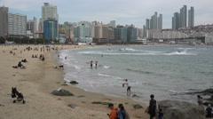 People visit popular beach in Busan, leisure activities in South Korea Stock Footage
