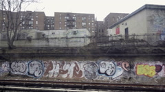 Subway graffiti wall poverty stricken ghetto neighborhood Brooklyn NYC Stock Footage