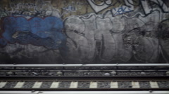 graffiti on wall passing from moving subway train view above gritty tracks NYC - stock footage