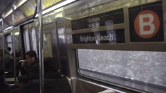 B train interior Harlem Brighton Beach sign passengers sitting window NYC subway Stock Footage