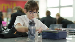 4K Sad boy eating lunch alone in school cafeteria - stock footage