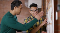4K Cheerful hipster business people looking at pin board in creative office - stock footage