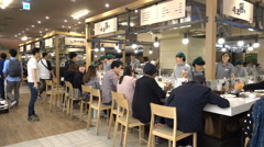 Popular food court, open kitchen, people eating dinner, South Korea - stock footage