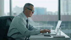 elderly businessman look at phone and working with computer in modern office - stock footage