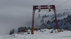 Ski lift lifts people to the top of the mountain in fog weather. Stock Footage
