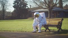 4K Sad astronaut lost in a park on earth Stock Footage
