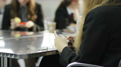 4K School girls looking at mobile phones during lunch break in school cafeteria Stock Footage