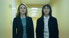 Two businesswoman standing in corridor in office building Stock Footage