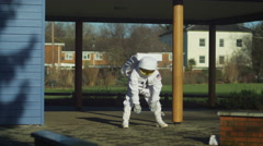 4K Funny astronaut doing stretches and warm up exercises in street Stock Footage