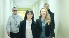Group of business people walking down the corridor in modern office building Stock Footage
