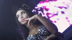 Girl in mouse ears, crystals top posing on camera in nightclub. Hand at face - stock footage