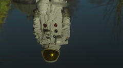 4K Astronaut exploring earth & looking at his reflection in a puddle Stock Footage