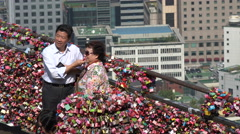 Tourists take pictures with colorful love padlocks in Seoul, South Korea Stock Footage