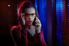 Portrait of an inquisitive woman talking on the phone - stock photo
