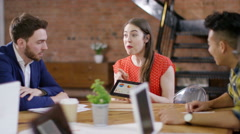 4K Business team in a meeting looking at sales figures & clapping their success. - stock footage