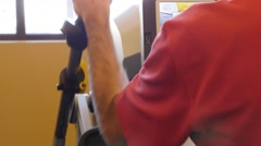 A man using a sitting stair machine in gym Stock Footage
