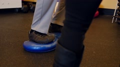 Man practices balance in physical therapy dolly shot Stock Footage