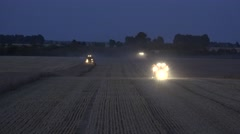 Combines and tractors with lights cultivating cereal corn field at night. 4K Stock Footage