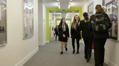4K Teachers & young students chatting & walking through busy school corridor Stock Footage