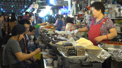 Open restaurant, vendors serve local delicacies at night market in Seoul, Korea Stock Footage