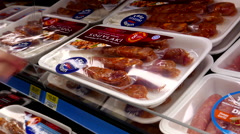 Woman buying pork sirloin kabobs value pack inside Walmart store - stock footage
