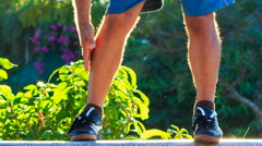 Closeup Man Does Morning Exercises Bends to Feet in Park - stock footage