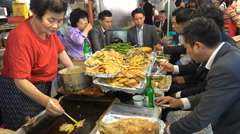 Business friends enjoy a late night dinner at a popular market in Seoul, Korea Stock Footage