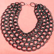 Necklace from strings of black chain on pink Stock Photos