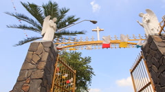 Gate with Cross God Statues to Catholic Church by Palm - stock footage