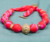 necklace from red silk and bronze beads on gree - stock photo