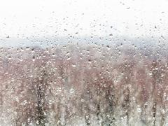 water drops from melting snow on home windowpane - stock photo